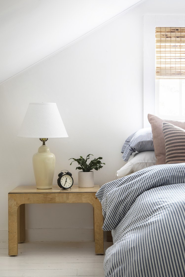 Blue and white striped bed cover; wood nightstand with yellow lamp