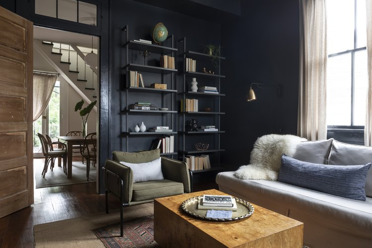 Blue painted den with open shelving unit and wood coffee table