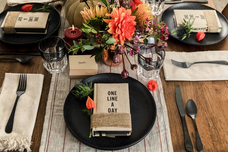 Rustic table setting with black plates and flatware