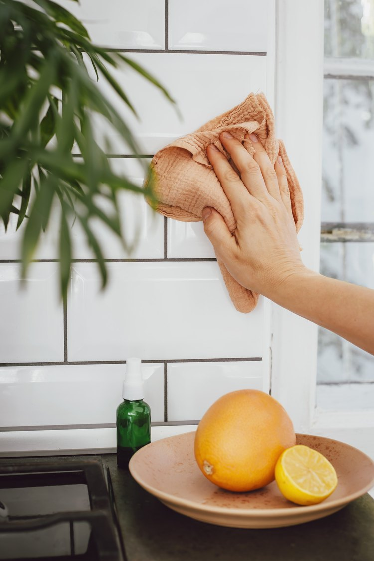 person cleaning kitchen tiles