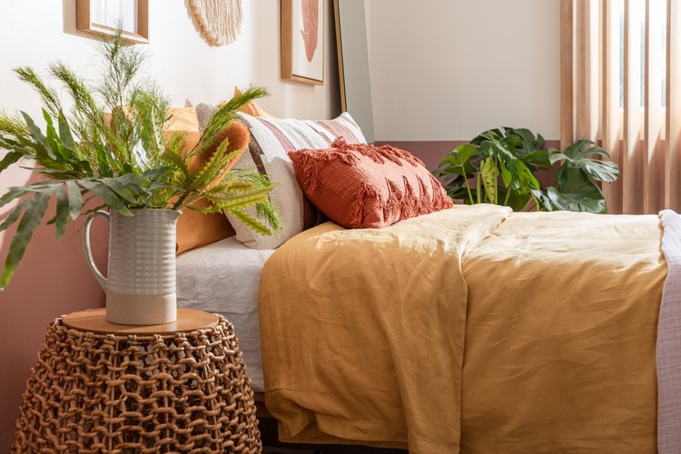 bed with yellow quilt surrounded by plants