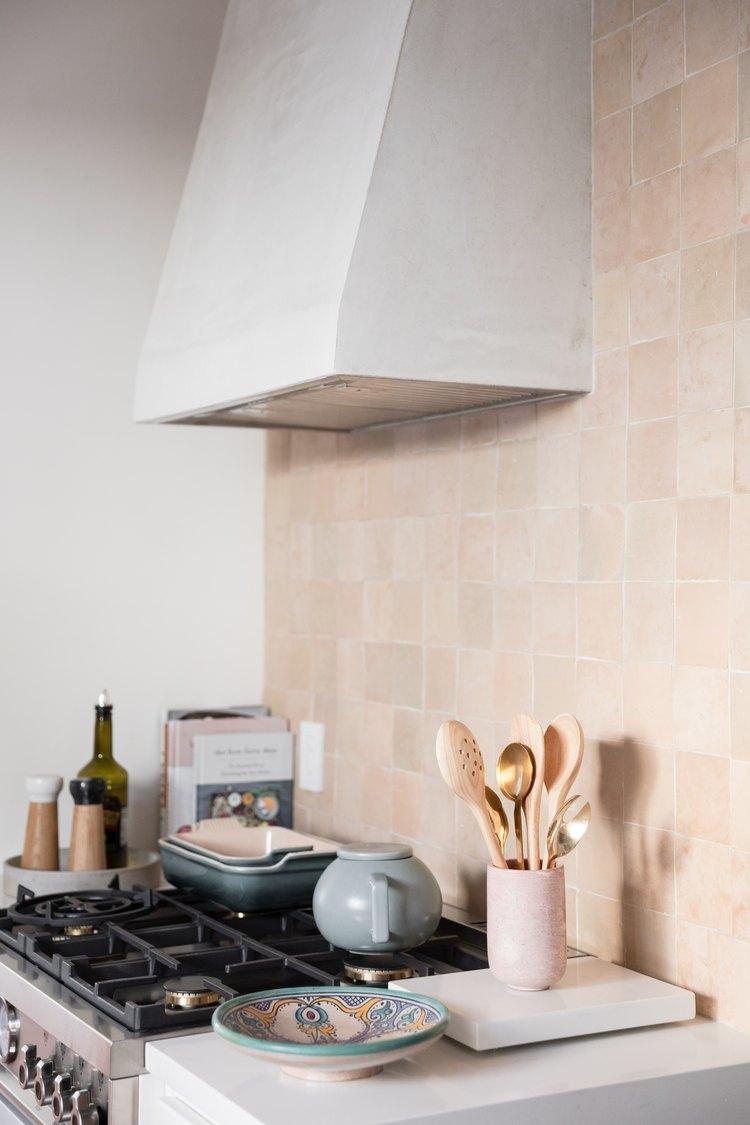 kitchen oven and hood with blush backsplash