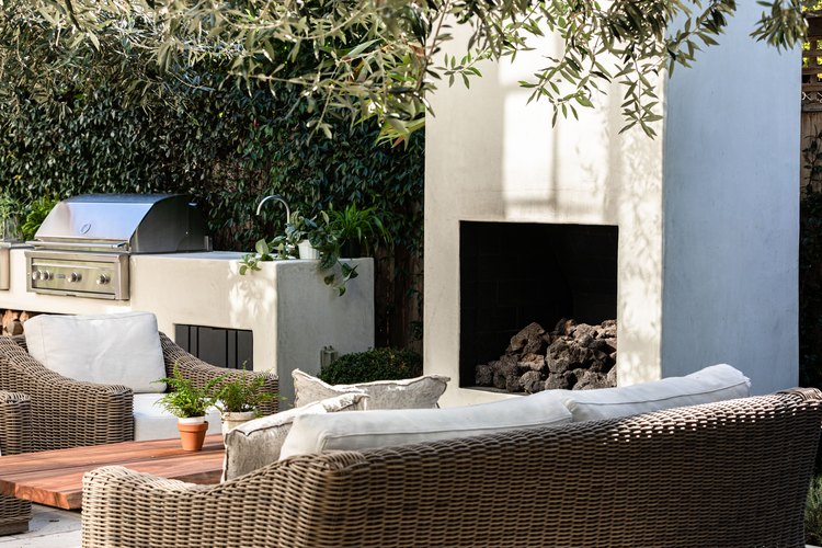 A patio with a fireplace, grill and white cushioned wicker seating