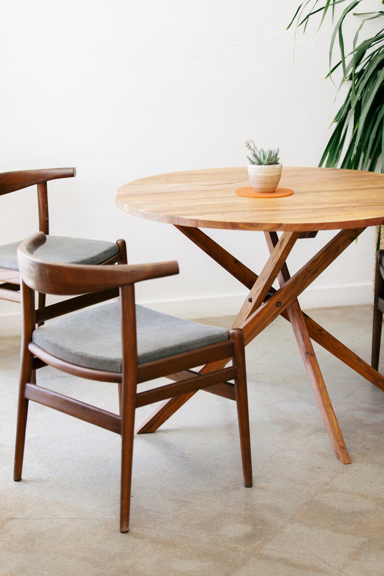 a midcentury outdoor dining set with sturdy dark brown chairs and a round table with criss-crossing legs