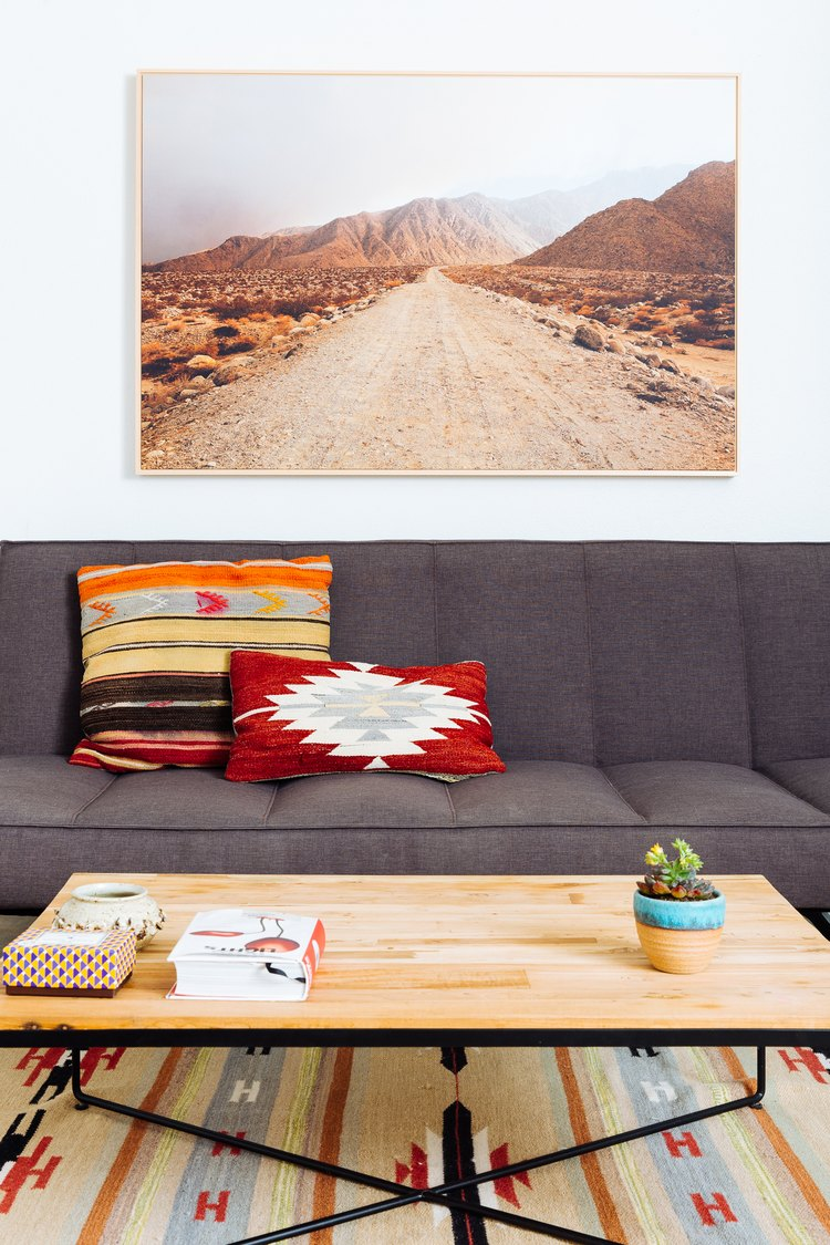 a desert landscape hangs above a a gray couch and a coffee table with a wooden top