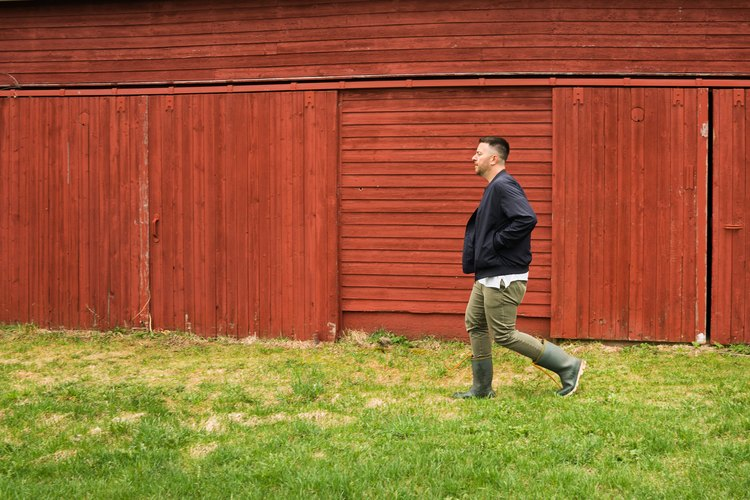 a man walks across green grass in front of a red barn