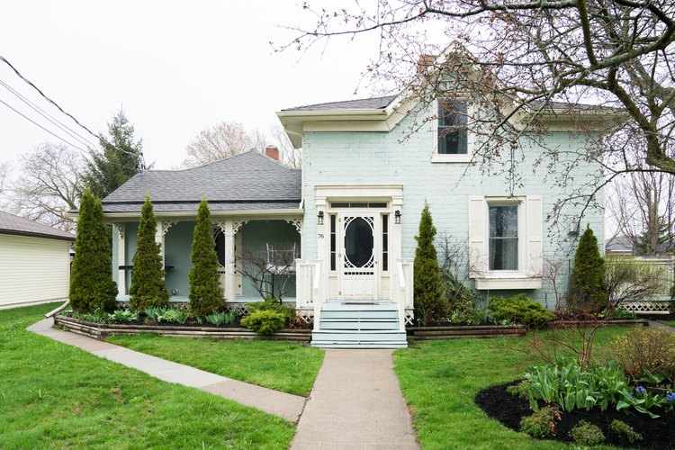 a sea-foam green two-story victorian house with a lush green lawn and a front door with a large glass pane