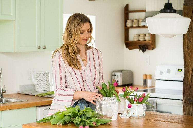 a woman places tulips in a vase in a kitchen with rustic pine countertops