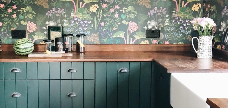 Kitchen wallpaper idea with green cabinets and floral print
