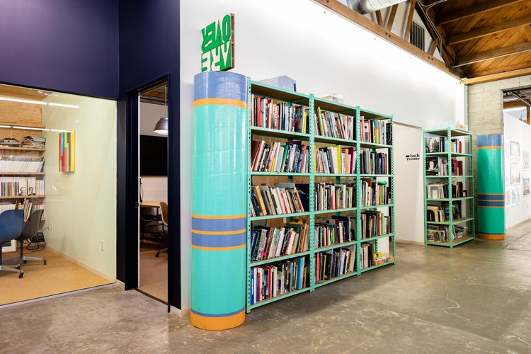Large turquoise book against wall in open space with cement floor