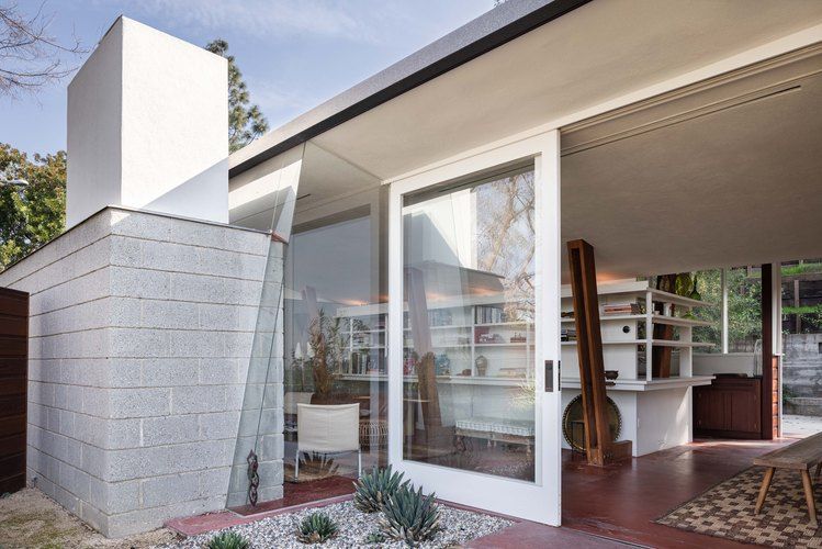 Midcentury home by John Lautner with sloped wooden beams and vintage couch with white bookcases and large glass doors