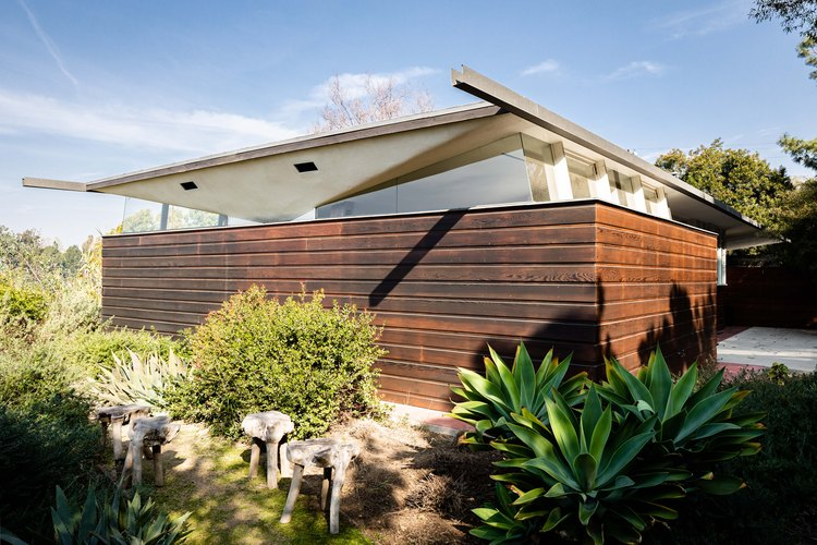 Exterior of midcentury home by John Lautner with wood fencing and native plants