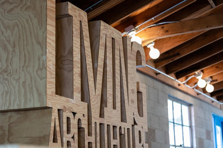 Wood art sculpture of letters below wood-beam ceilings