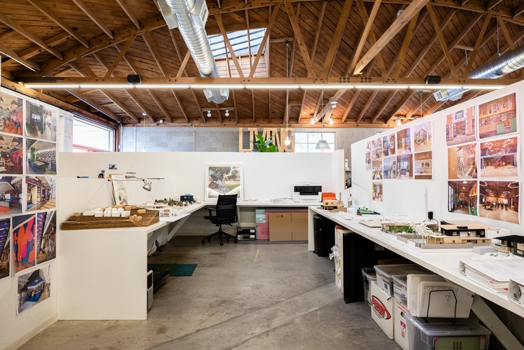 Office space with white texts and walls below high wood-beam ceilings