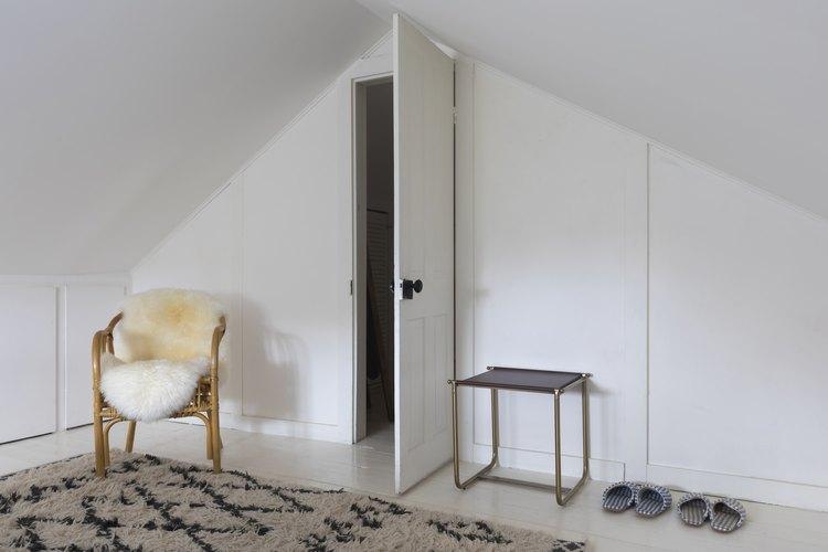 Open closet door next to chair with sheepskin rug