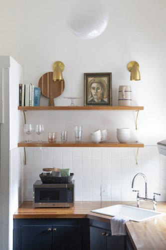 Open shelving in kitchen with brass sconces and wood countertop