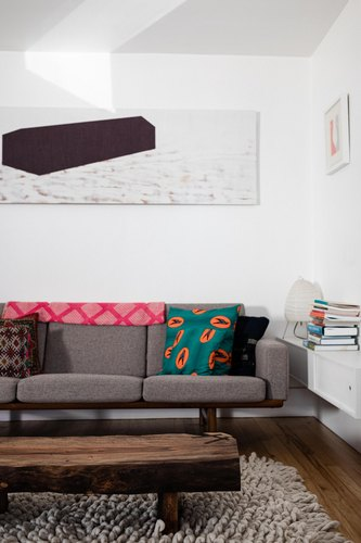 Grey sofa with artwork on wall and wood coffee table