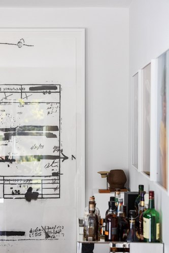Large ink illustration in frame on white wall next to bar