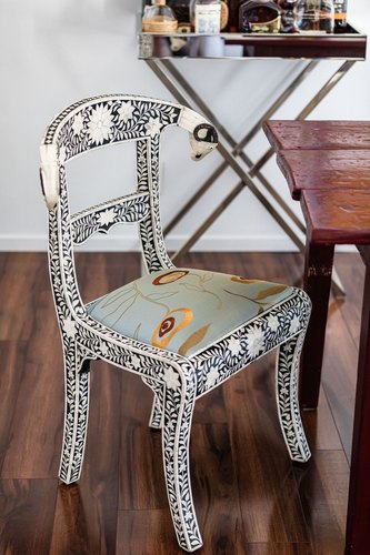 Decorative chair with silk embroidered seat next to wood table