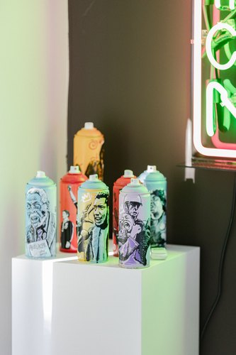 Illustrated spray paint cans on white pedestals