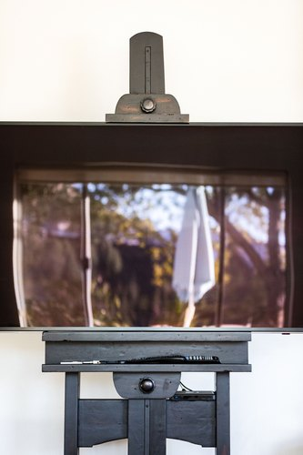 Flat-screen television on black easel against white wall