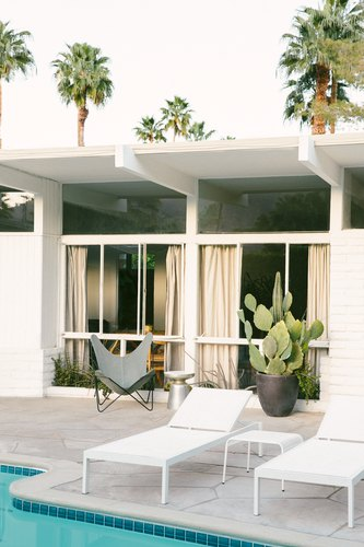 white chaise lounges on a pool deck with a butterfly chair and a large potted cactus