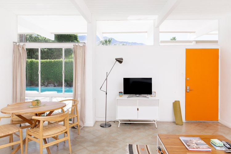 an entry area featuring a white entertainment console, mid-century swing-arm lamp and a bright orange door