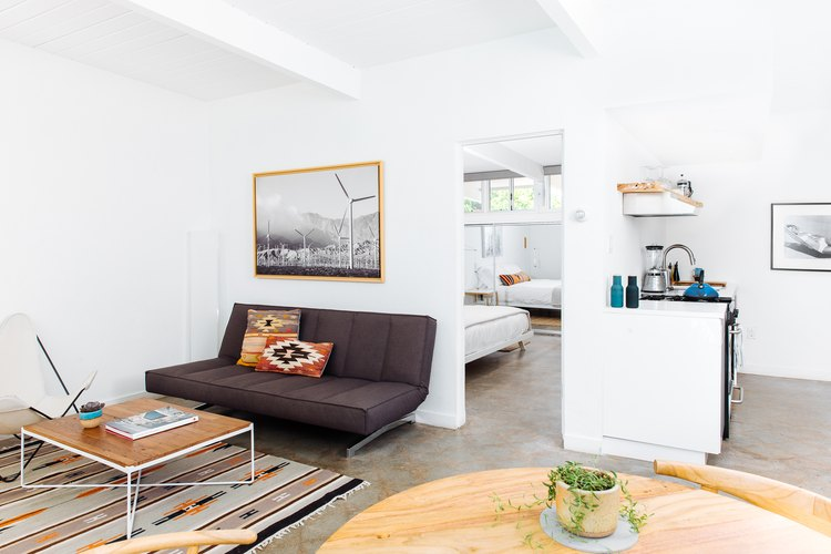 a living room area with a low, brown, mid-century couch, a wooden topped coffee table, and a southwestern rug