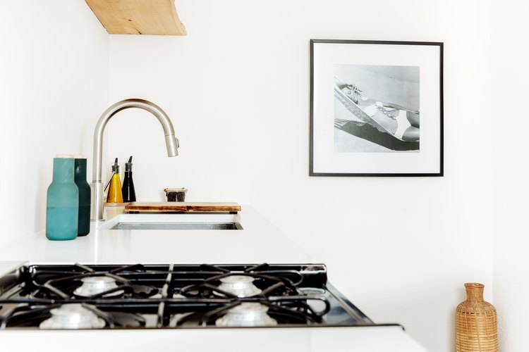a stark white kitchen features a framed photo of a woman in a bikini lounging in a hammock