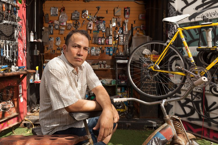 A person sitting in a workshop with bicycles and worship tools