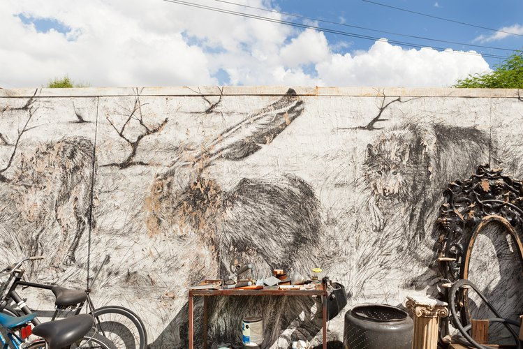 A mural of animals with a worktable, bicycle and a sculpture