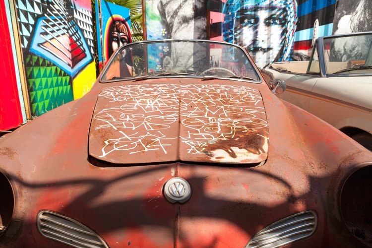 A brown retro car surrounded by colorful murals