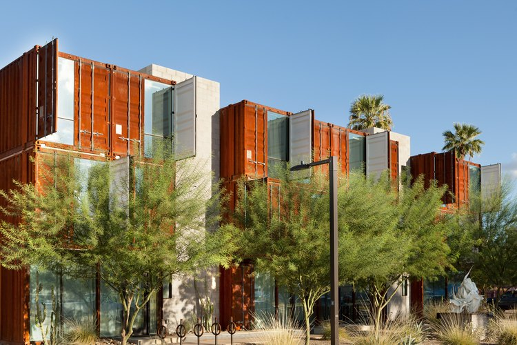 Brown-blue shipping container buildings with trees