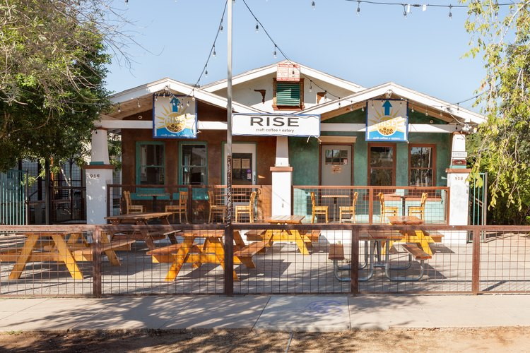 A white restaurant with wood picnic benches and a wood fence
