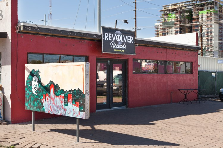 A red business with multiple windows and a mural in front