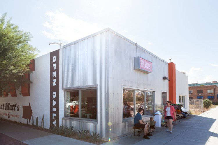 A restaurant with corrugated metal and orange-brown signage