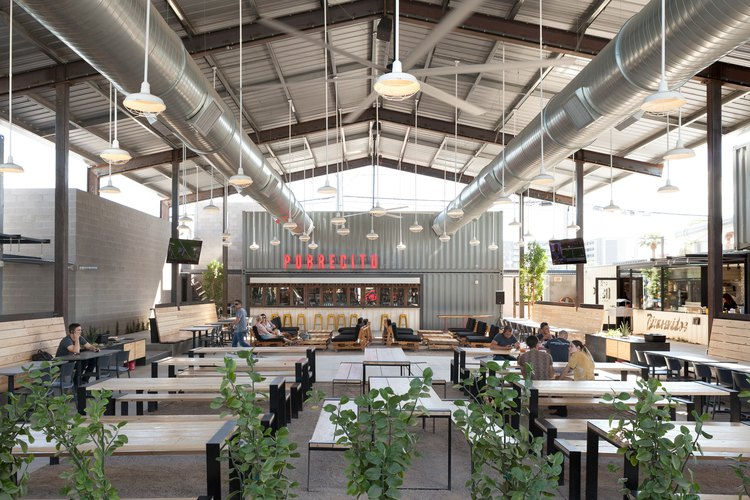 A bar in an industrial building with white pendant lights and wood tables