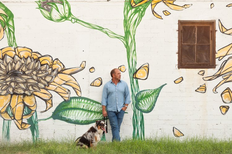 A person with a dog in front of a building wall with a painted sunflower mural