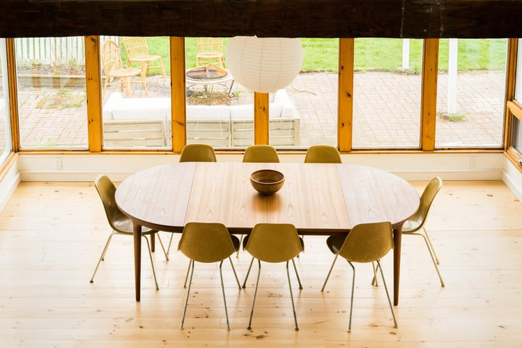 a oval dining table surrounded by mid-century molded plastic chairs