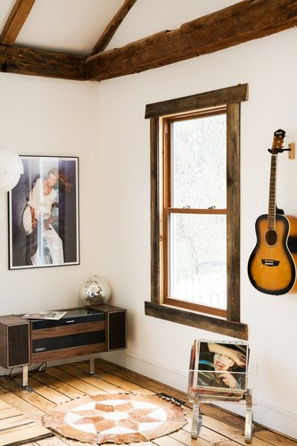 a half-timbered room with a guitar on the wall, vintage stereo equipment, and a rack of vinyl albums