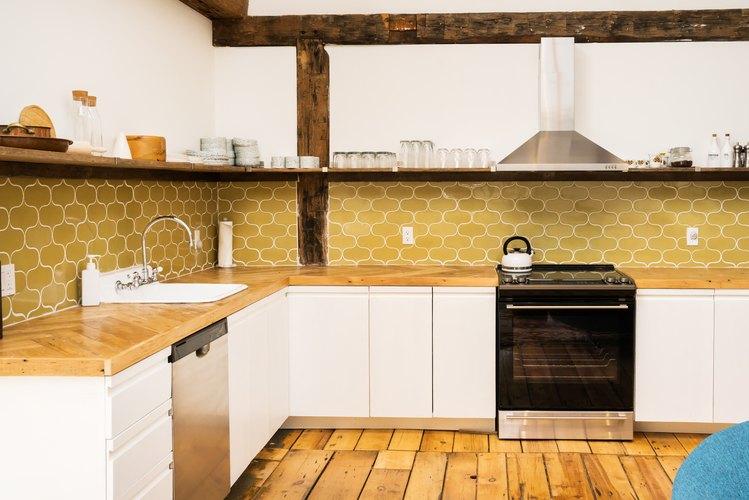 a kitchen with open shelving, wide-planked wooden floors, and a harvest-gold tile backsplash