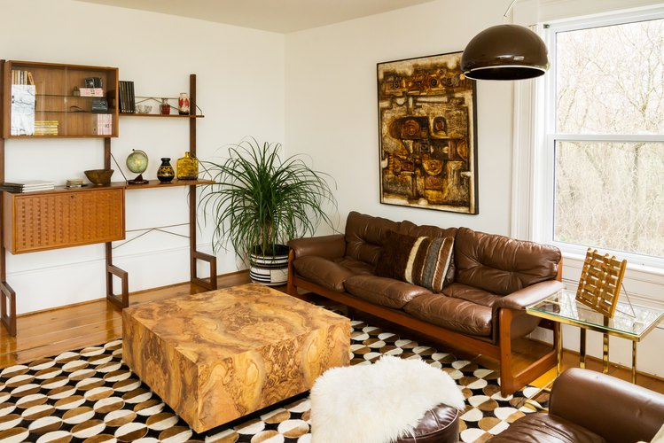 a brown leather couch and a marbled square coffee table in a room with brown abstract art and aa carpet with semi-circular patterns