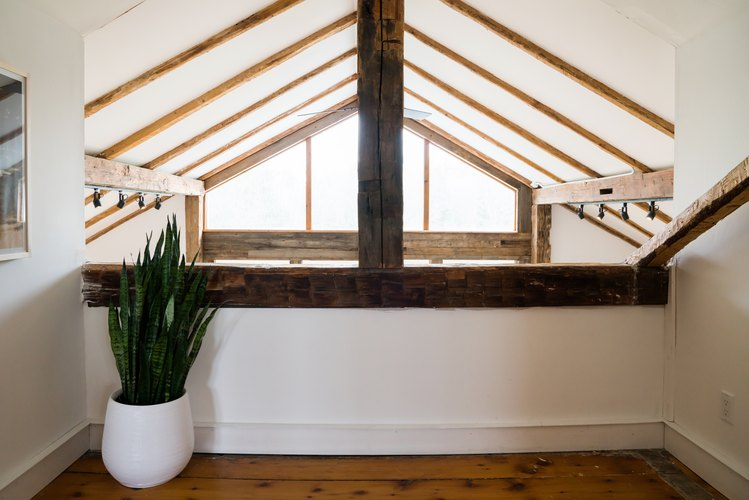 a triangular window under a sloped, half-timbered ceiling