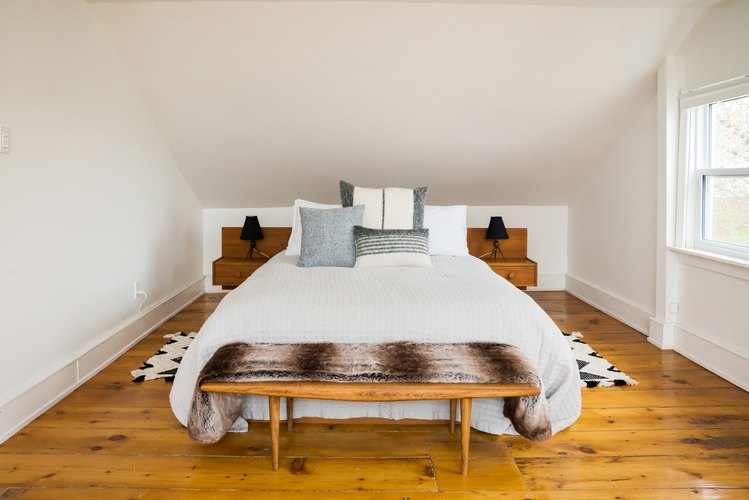 a white bedroom with a rustic wide-plank floor, a wooden bench at the foot of the bed, and matching built-in nightstands