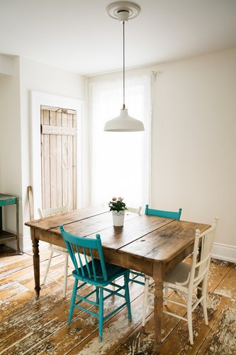 a dining table in a room with a wood floor, both made from wide rustic planks