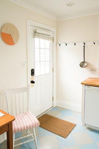 a spare white kitchen with a numberless clock on the wall and a giant ladle hanging from a hook