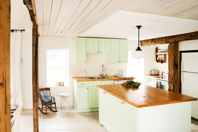 a half-timbered kitchen with a wooden ceiling, a pine-topped island, wood floors, green cabinets, and a wooden ceiling