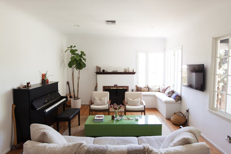 Living room with piano, green coffee table, built-in, and bohemian pillows